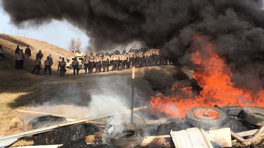 Tires burn as law enforcement officers stand in formation to force Dakota Access pipeline protesters off private land.