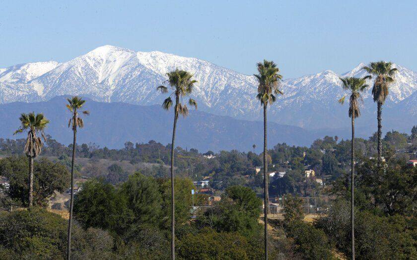 FILE - This Jan. 12, 2016 file photo shows the snow-capped San Gabriel Mountains, with Mount Baldy the highest peak at the left, seen from Chinatown near downtown Los Angeles. Authorities have closed trails at Baldy following the death of the second hiker in a week. San Bernardino County sheriff's