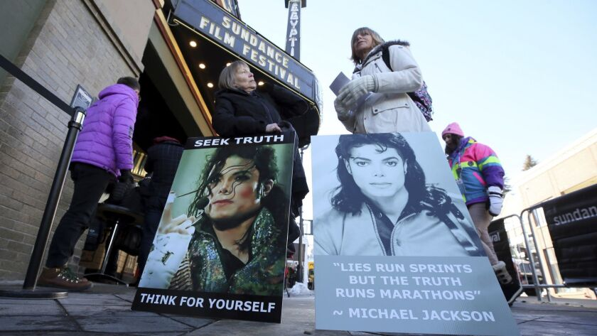 "Brenda Jenkyns, left, and Catherine Van Tighem who drove from Calgary, Canada, stand with signs outside of the premiere of the ""Leaving Neverland"" at the Sundance Film Festival."