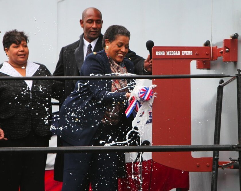 Myrlie Evers christens a dry cargo ship named for her late husband by smashing a bottle of champagne against the hull during a ceremony Saturday at General Dynamics-NASSCO in San Diego.