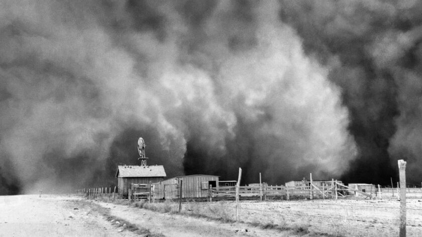 A farm with huge dust cloud approaching in Boise City, Oklahoma on April 15, 1935.