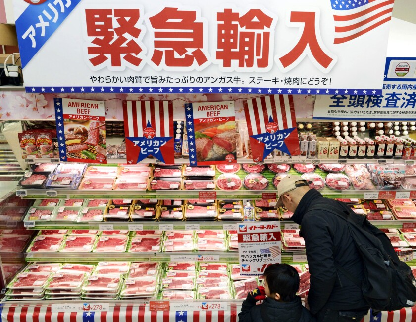 """FILE - In this Feb. 16, 2019, photo, packs of frozen beef imported from the U.S. are sold at a supermarket in Tokyo. Japan's Parliament has approved a trade deal that was agreed upon by President Donald Trump and Japanese Prime Minister Shinzo Abe earlier this year. The deal cutting tariffs between the countries takes effect at the beginning of next year. Some critics say the deal is more advantageous to the U.S. since a 2.5% tariff on Japanese automobiles remains. The deal will pave the way for cheaper American beef and other agricultural products in Japan. The banner in the background reads: """"Emergency import."""" (Kyodo News via AP, File)/Kyodo News via AP)"""