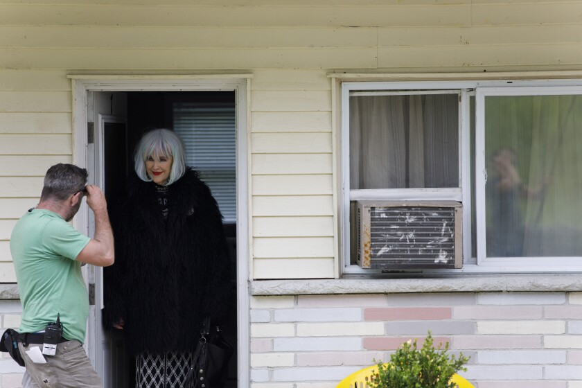 "Catherine O'Hara peers out of a doorway between takes on the set of ""Schitt's Creek."""