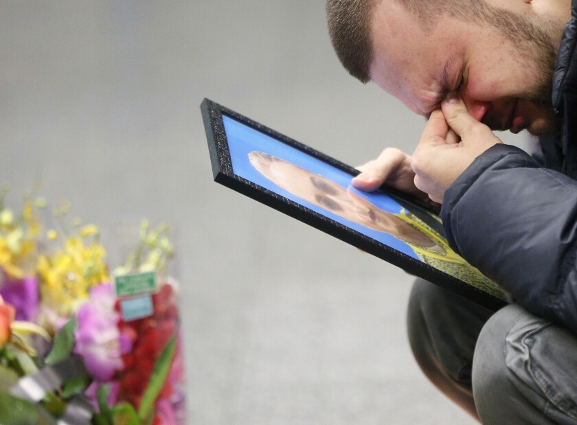 FILE - In this Jan. 10, 2020 file photo, the partner of Julia Sologub, a member of the flight crew of the Ukrainian 737-800 plane that crashed on the outskirts of Tehran, reacts as he holds a portrait of her at a memorial inside Borispil International Airport outside Kyiv, Ukraine. More questions than answers remain about the disaster that killed 176 people on board the Ukrainian jetliner, a year after Iran's military mistakenly downed the plane with surface-to-air missiles. Officials in Canada, which was home to many of the passengers on the doomed plane, and other affected countries have raised concerns about the lack of transparency and accountability in Iran's investigation of its own military. (AP Photo/Efrem Lukatsky, File)