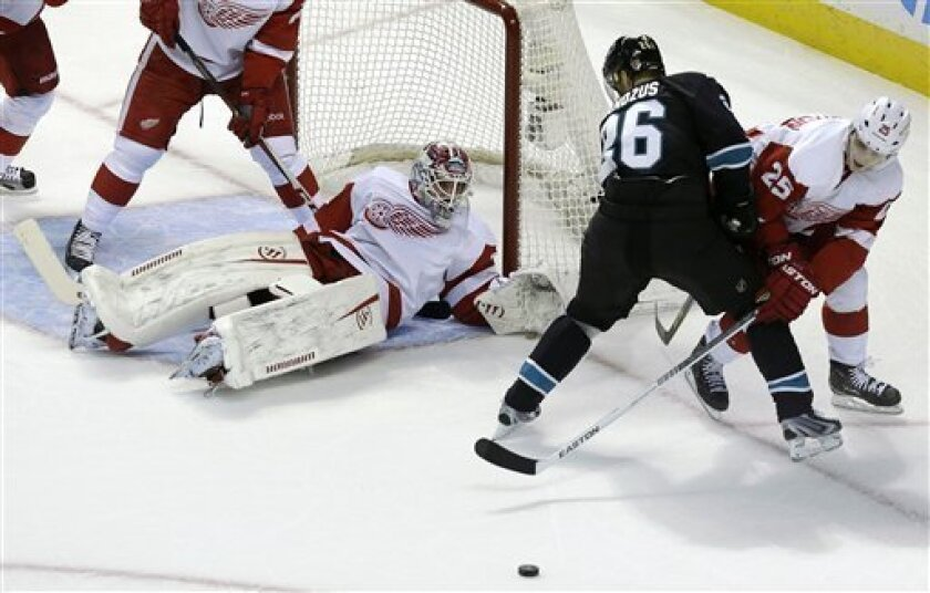 Detroit Red Wings goalie Jonas Gustavsson, third from right, from Sweden, watches in front of the net as center Cory Emmerton (25) and San Jose Sharks center Michal Handzus (26), from Slovakia, look for the puck during the first period of an NHL hockey game in San Jose, Calif., Thursday, Feb. 28, 2