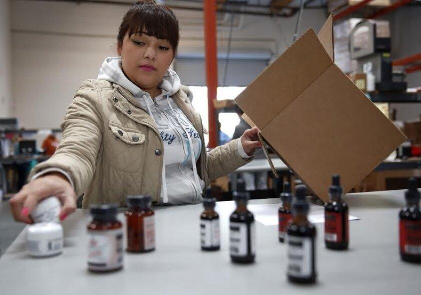 Medical Marijuana Inc. employee Celina Mejia prepares products for shipping at the company's Poway facility.