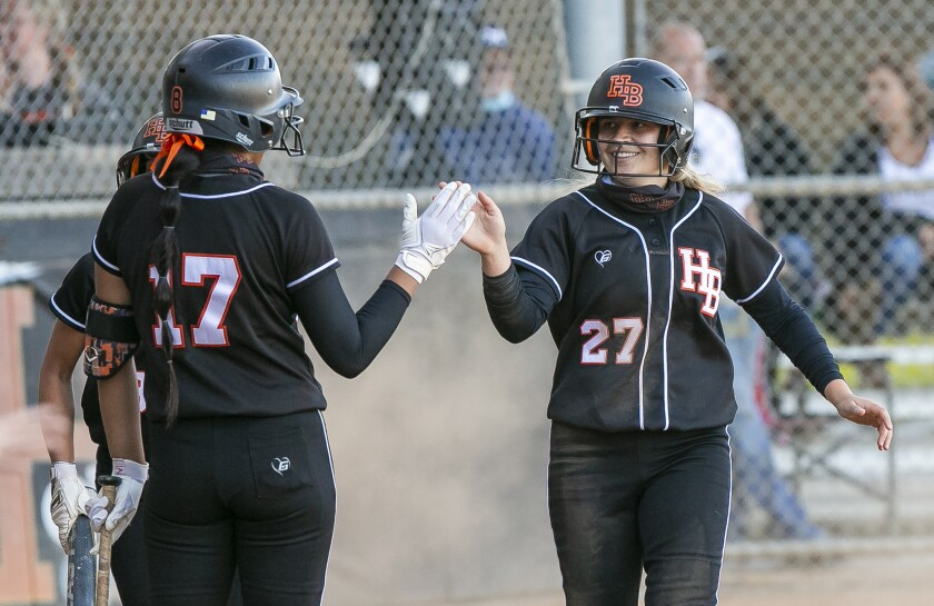 Huntington Beach's Jaylene Duarte, left, high-fives Zoe Nakutis  during a softball game against Marina on April 28.