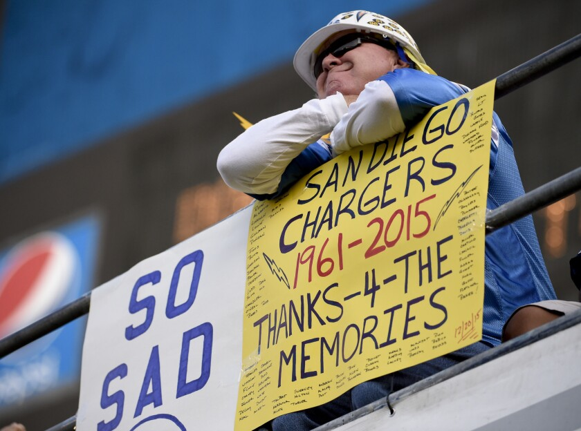 A fan holds up a sign on Dec. 20 commenting on the possible move by the San Diego Chargers.