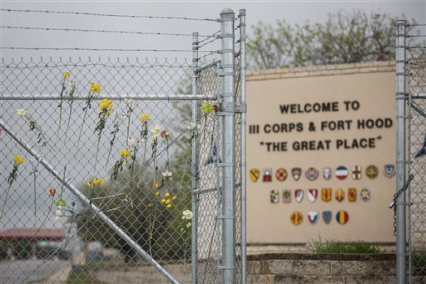 Flowers decorate a fence outside Ft. Hood's east gate in Killeen, Texas, in honor of those killed and wounded in Wednesday's shooting.