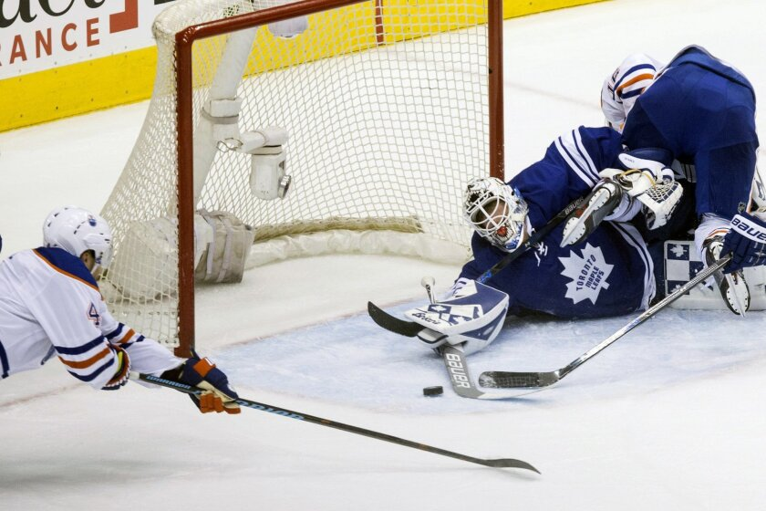 Toronto Maple Leafs goaltender Garret Sparks, center, and Edmonton Oilers' Taylor Hall, left, stretch to reach a puck after Sparks made a save on Oilers' Teddy Purcell, right, during the second period of an NHL hockey game in Toronto on Monday, Nov. 30, 2015. (Chris Young/The Canadian Press via AP)
