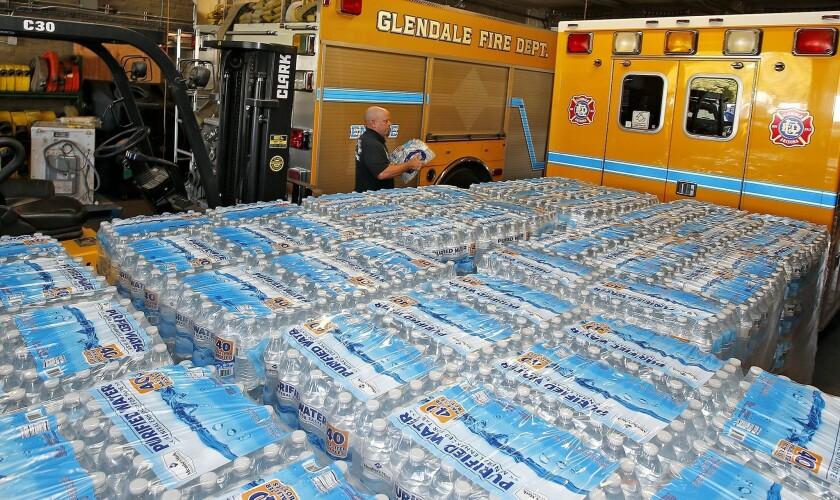 El oficial Chris Greene carga un paquete de agua embotellada junto a decenas de paquetes mientras el Centro de Recursos del Departamento de Bomberos de Glendale para un calor que se espera imponga récord el fin de semana, en Glendale, Arizona. (AP Foto/Ross D. Franklin)