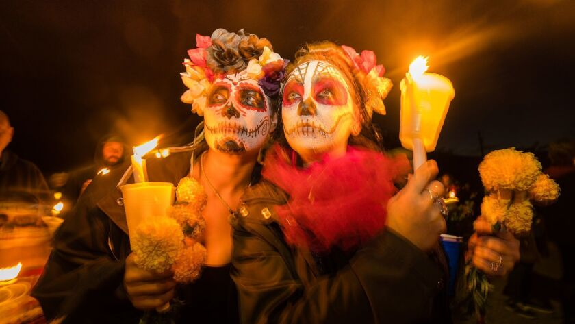 Some of this year's celebrants in Hornitos, with painted faces and marigolds, remember the dead.
