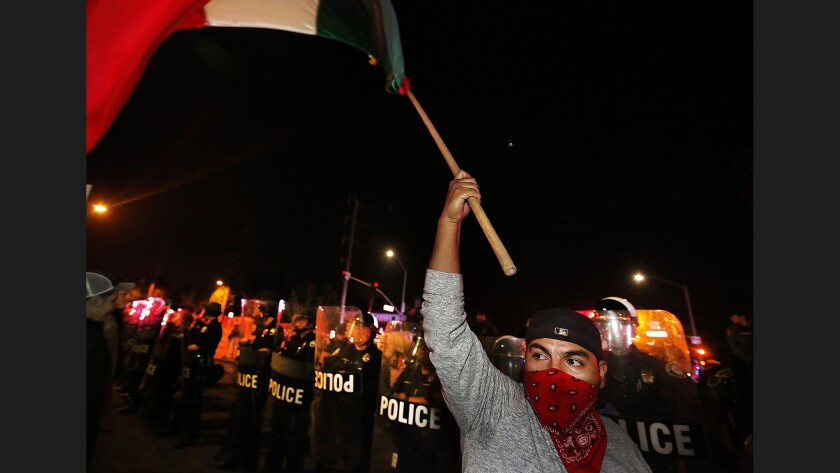 A protester waves a flag before a phalanx of police officers in riot gear.