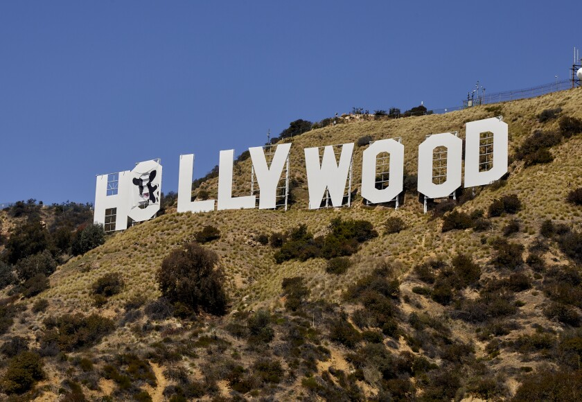 """The Hollywood sign with a cow painting draped over the first """"O."""""""