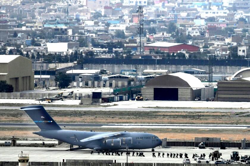 U.S. service members board an Air Force aircraft Monday at the Kabul airport.