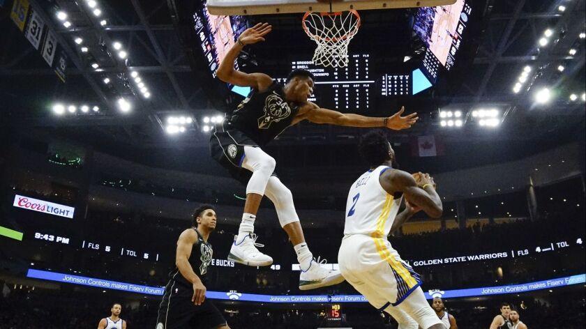 Golden State Warriors forward Jordan Bell is harassed by Milwaukee Bucks forward Giannis Antetokounmpo on Friday night at Fiserv Forum in Milwaukee.