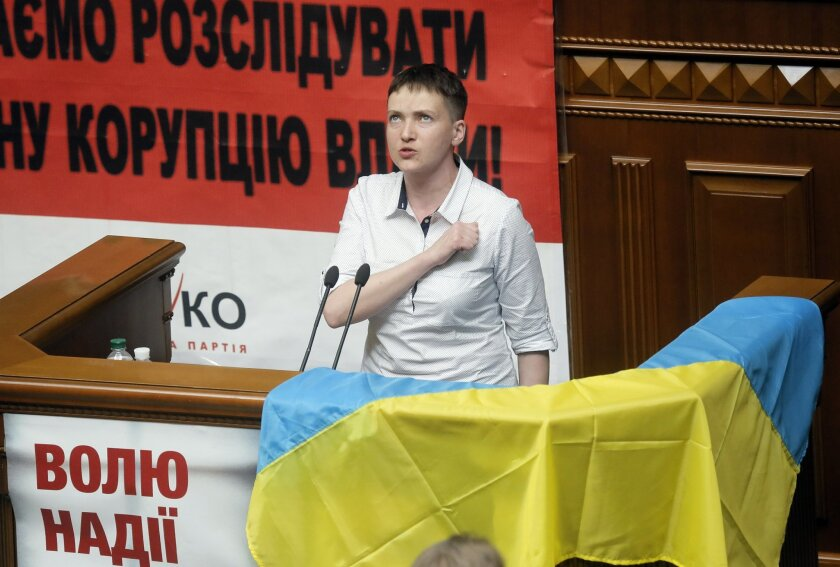 """Ukrainian pilot Nadiya Savchenko sings the national anthem during the parliament session in Kiev, Ukraine, Tuesday, May 31, 2016. Savchenko appeared for her first session at the Ukrainian parliament as a lawmaker in former Prime Minister Yulia Tymoshenko's party on Tuesday. The poster reads: """"Freed"""