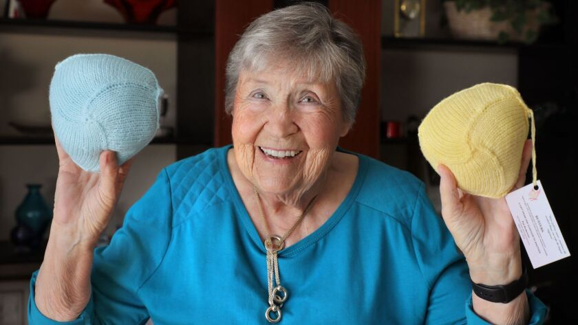 "Pat Anderson holds two of her ""Busters"" wardrobe accessories she knitted for breast cancer survivors."