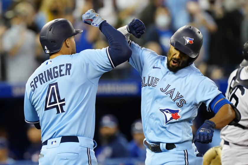 Toronto Blue Jays second baseman Marcus Semien, right, celebrates his home run against New York Yankees starting pitcher Gerrit Cole with teammate center fielder George Springer (4) during the first inning of baseball game in Toronto on Wednesday, Sept. 29, 2021. (Frank Gunn/The Canadian Press via AP)