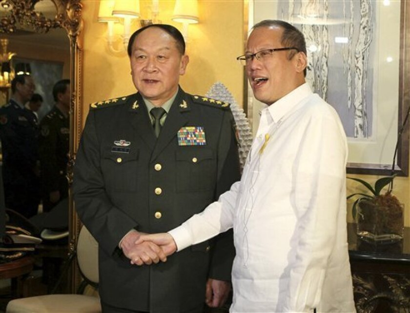 In this photo taken on May 23, 2011 and released by Malacanang Palace, Philippine President Benigno Aquino III, right, welcomes Chinese Defense Minister Gen. Liang Guanglie, at Malacanang Palace in Manila, Philippines. While Liang was shaking hands with Aquino III and clinking wine glasses with Manila's military brass during the May 23 visit, three Chinese Navy ships were erecting a steel post about 290 kilometers (180 miles) offshore to fortify their claim to a reef in the disputed South China Sea, according to a Philippines military report. The Philippines and Vietnam accused Chinese ships of interfering with energy exploration efforts this year. (AP Photo/Malacanang Photo Bureau, Gil Nartea) NO SALES, EDITORIAL USE ONLY