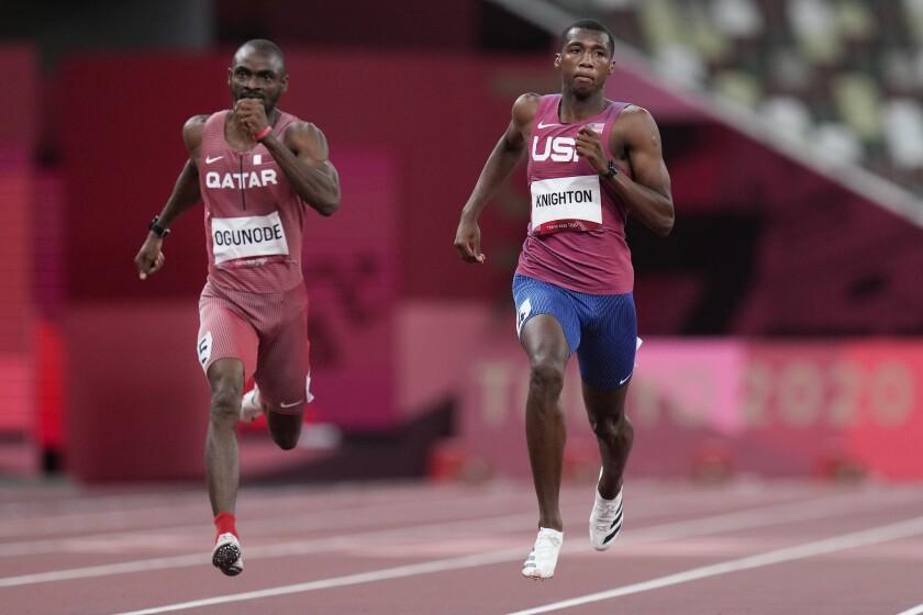U.S. sprinter Erriyon Knighton, right, and Qatar's Femi Ogunode race to the finish line in a men's 200-meter semifinal.