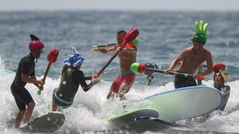 Surfers battle while riding a wave during the 10th annual Switchfoot Bro-am's nerf surf jousting exposition at Moonlight Beach in Encinitas on Saturday. (/ Hayne Palmour IV)