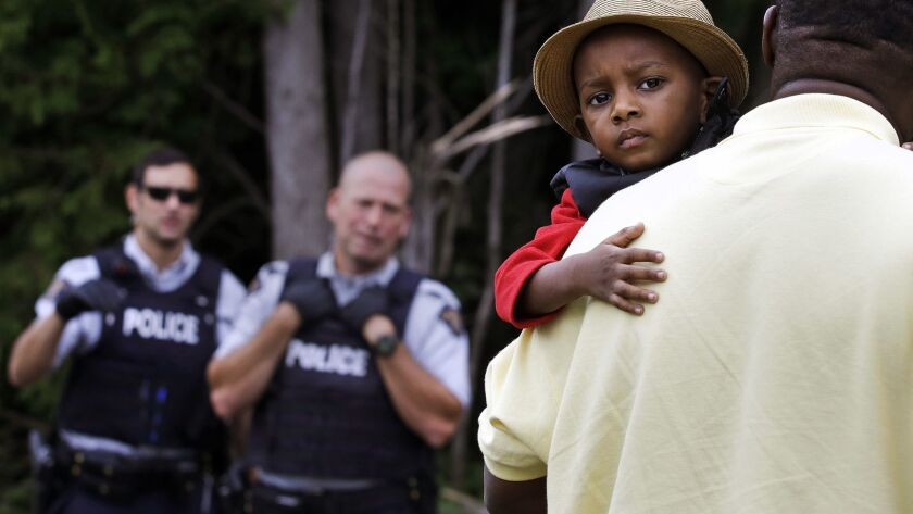 A Haitian boy holds onto his father as they approach an illegally crossing point, staffed by Royal C