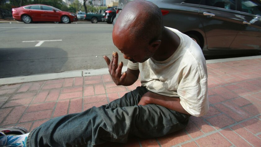 Wadell Robinson, 50, wakes up on a sidewalk in downtown San Diego on Aug. 10, 2016. Robinson, who said he was diagnosed with schizophrenia in his 20s, repeatedly has had his belongings stolen and wants a cot to sleep indoors somewhere.