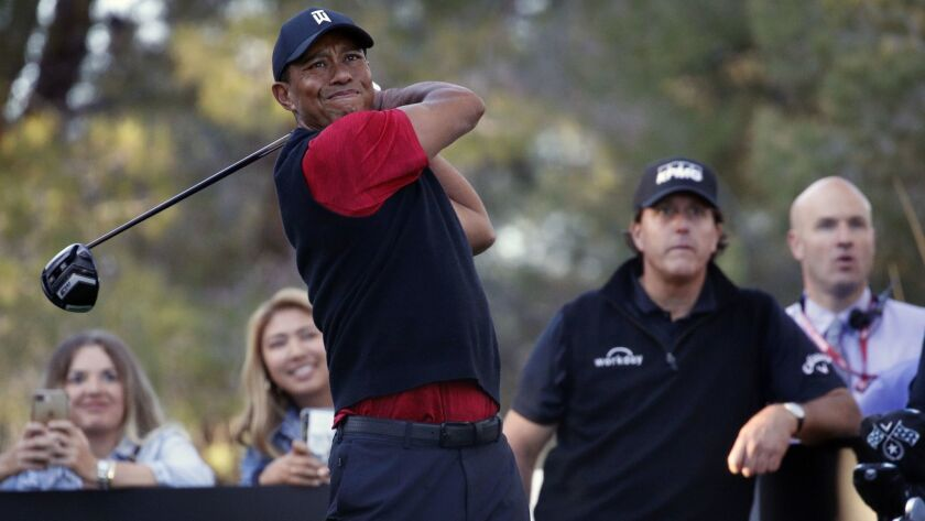 Tiger Woods hits off the 16th tee as Phil Mickelson watches during a golf match at Shadow Creek golf
