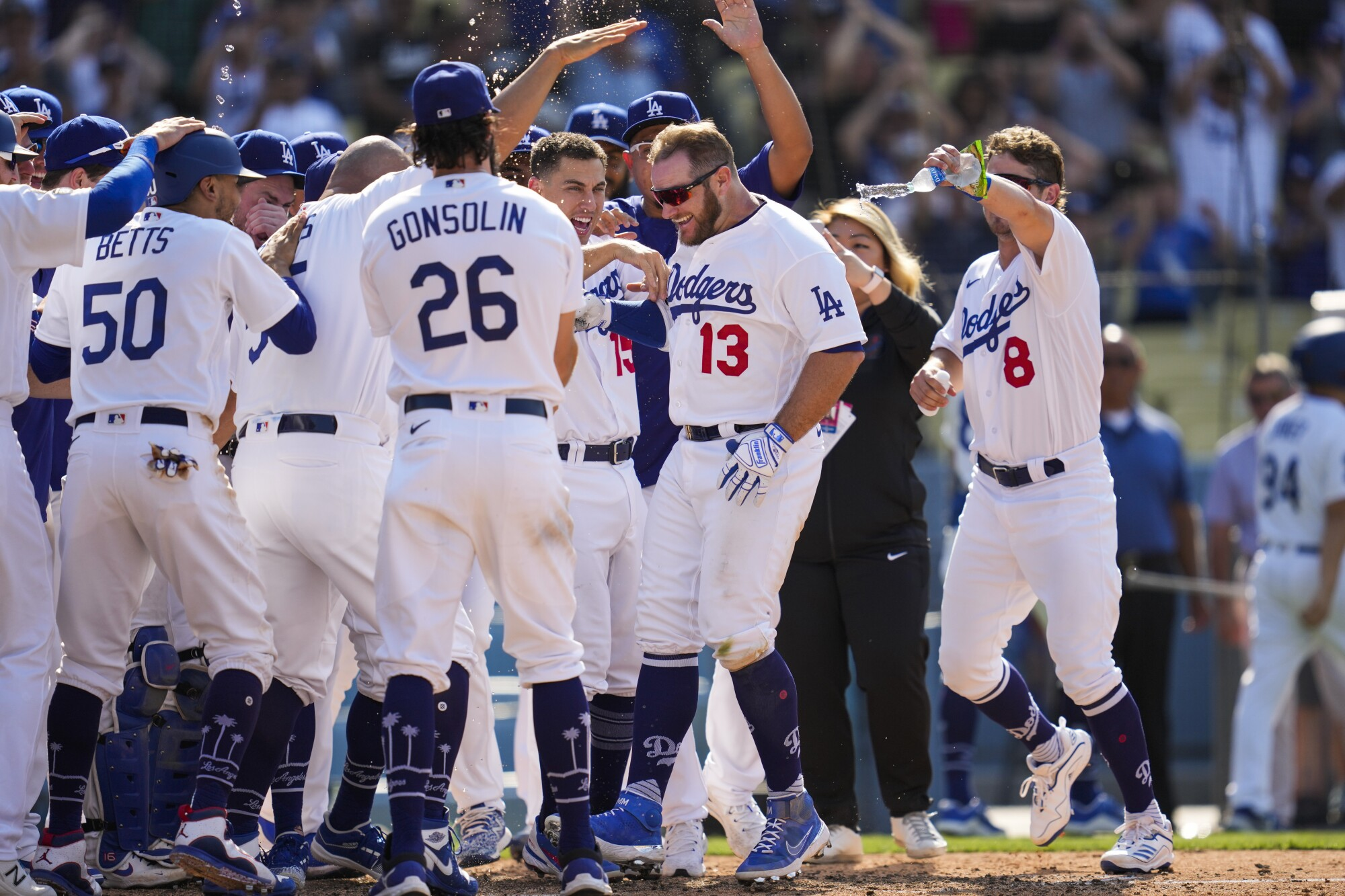 Max Muncy (13) celebrates with his Dodgers teammates after hitting a walk-off home run in a 7-4 victory.