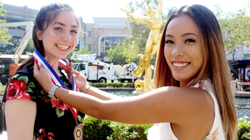 Rita Ohan, Spirit of American Youth Scholarship winner, is awarded a ribbon by Alea Chin, Americana