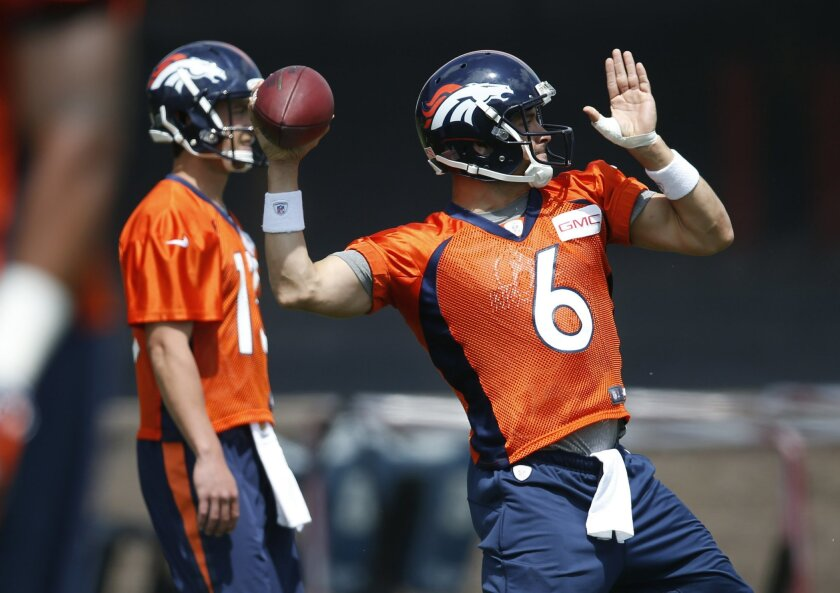 Denver Broncos quarterback Mark Sanchez, front, throws a pass as quarterback Trevor Siemian looks on during NFL football practice Tuesday, May 31, 2016, at the team's headquarters in Englewood, Colo. (AP Photo/David Zalubowski)