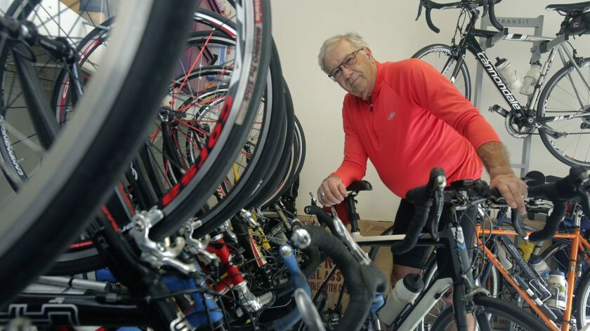 Dr. Daniel Marks of Carlsbad posed with some of 22 bicycles, which he takes turn riding during his thrice-weekly fitness rides.