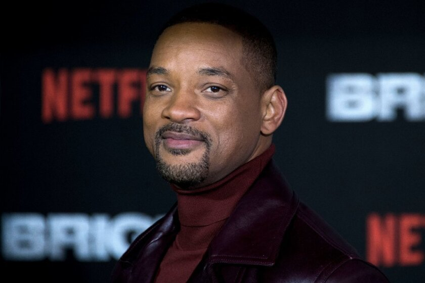 Will Smith in a red turtleneck and black jacket
