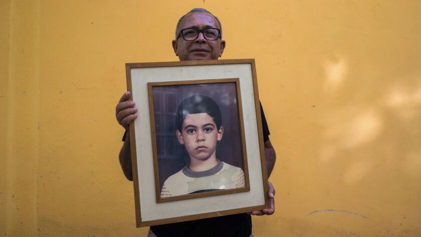 Francisco Luiz da Silva holds a photo of his son Guilherme Figueiredo da Silva, who disappeared afte