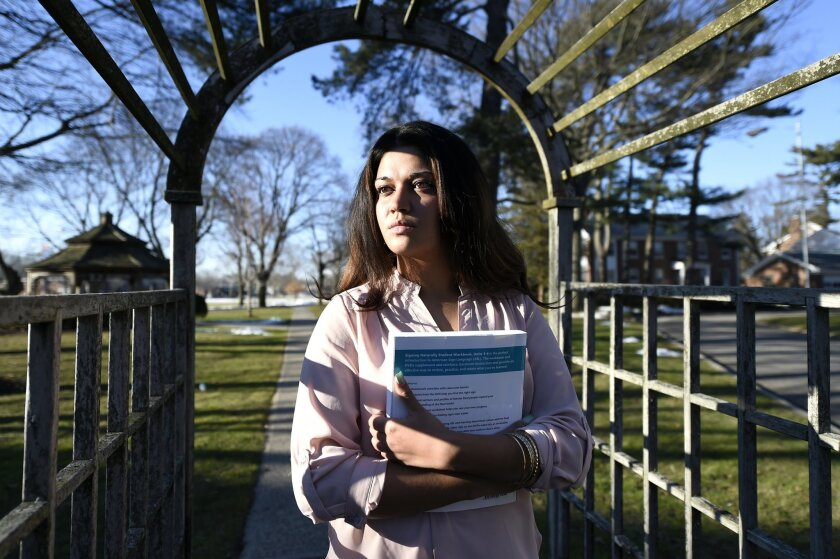 In this Feb. 2, 2016 photo, Naila Amin, 26, holds a book from one of the classes she is taking at Nassau Community College in Garden City, N.Y. Amin, who was forced into marriage at the age of 15 to a 28-year-old cousin in Pakistan who beat and mistreated her, aspires to become a social worker and