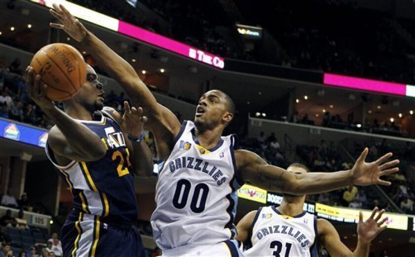 Utah Jazz's Paul Millsap, left, makes a pass around Memphis Grizzlies' Darrell Arthur, right, during the second half of an NBA basketball game in Memphis, Tenn., Monday, March 21, 2011. (AP Photo/ Mark Weber)