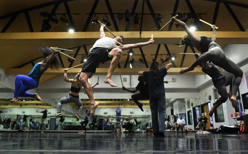 Dancers at Lula Washington Dance Theatre leap in the air in rehearsal.