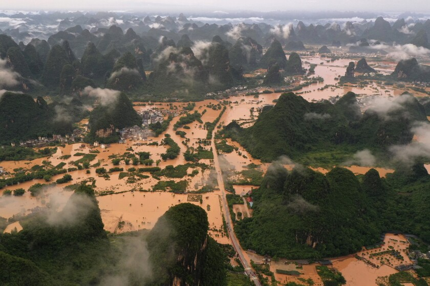 FILE - In this June 7, 2020, file photo released by China's Xinhua News Agency, floodwaters surround a village in Yangshuo in Guilin in southern China's Guangxi Zhuang Autonomous Region. Rainstorms have killed five more people in a southern Chinese region already reeling from heavy flooding over the past week. The government of Zunyi city, south of the metropolis of Chongqing, said Saturday that five had died and eight others were missing after fresh storms began late Thursday night. (Lu Boan/Xinhua via AP, File)