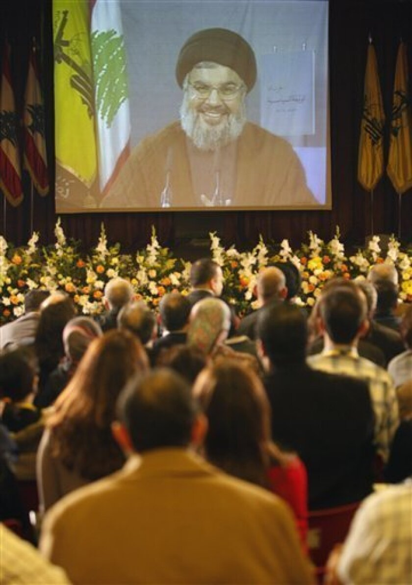 Hezbollah leader Sheik Hassan Nasrallah is seen speaking via a video link as journalists listen to him during a press conference in which he read the group's new political manifesto, the second since Hezbollah was born in the early 1980s, in the southern suburb of Beirut, Lebanon, on Monday Nov. 30