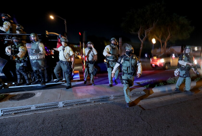 Los Angeles County sheriff's deputies disperse protesters marching in West Hollywood on Friday night.