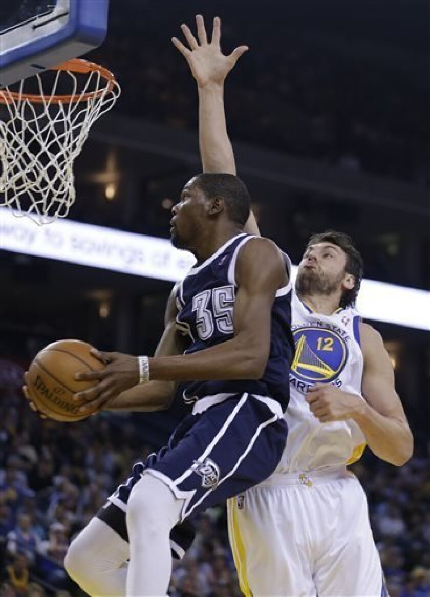 Oklahoma Thunder forward Kevin Durant (35) goes up for a shot against Golden State Warriors' Andrew Bogut during the first half of an NBA basketball game Thursday, April 11, 2013, in Oakland, Calif. (AP Photo/Ben Margot)