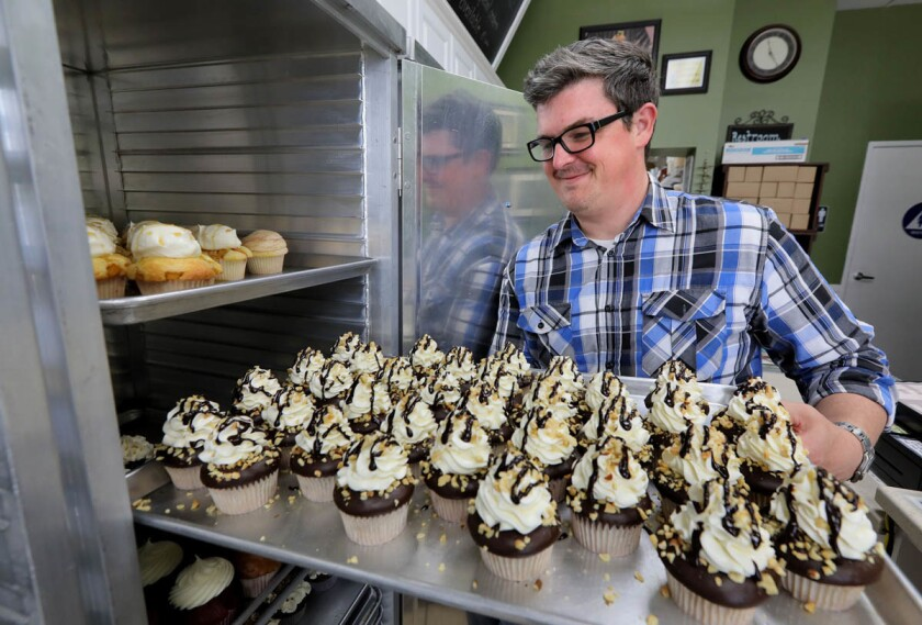 Don Hein, owner of Little Cakes Cupcake Kitchen, moves a fresh tray of Chocolate Dip Banana flavor cupcakes.