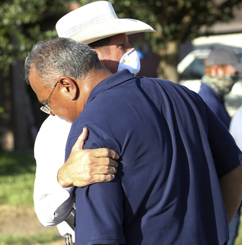 McAllen Police Chief Victor Rodriguez is hugged by a Texas Ranger after speaking at a news conference near the shooting site.