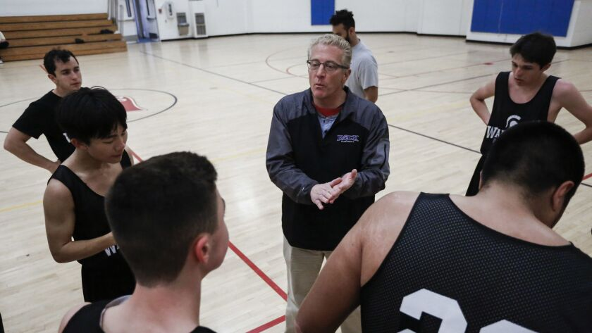 Rock Academy coach Keith Luberto, who's guided the Warriors to a 14-4 record this season, addresses the team at the Salvation Army gym in Clairemont.