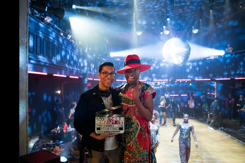 """Pose"" co-creator, writer and director, Steven Canals, poses with a director's clapperboard on the set of the FX show. He smiles with actor Billy Porter, as bright lights shine behind them."