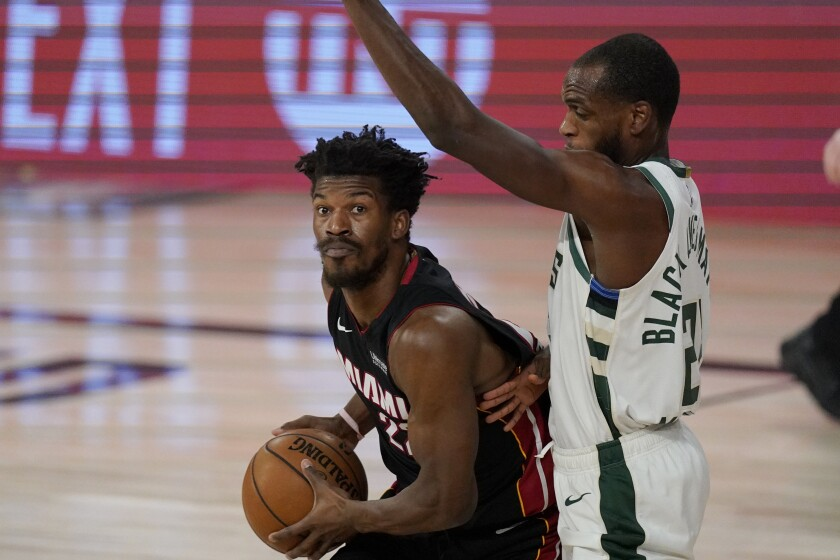Miami Heat's Jimmy Butler, left, drives against Milwaukee Bucks' Khris Middleton.