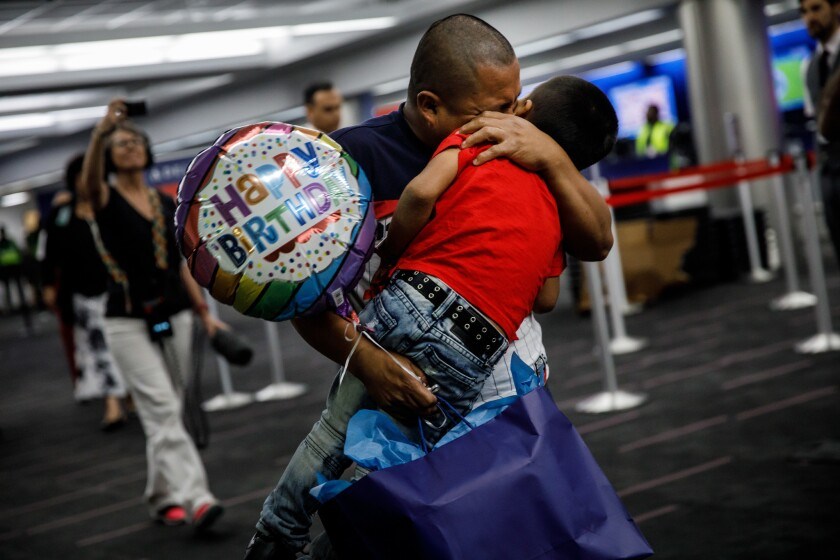 Guatemalan asylum seeker Hermelindo Che Coc embraces his 6-year-old son, Jefferson Che Pop, after reuniting with him at LAX.