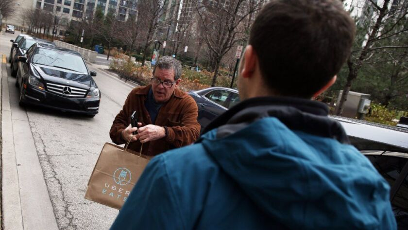 Uber Eats driver Jim Butler, left, delivers lunch to Orr Weinstein on Dec. 22, 2015, in Chicago. The ride-hailing company says the three-year-old service now covers about half the U.S. population, mainly in large metro areas.