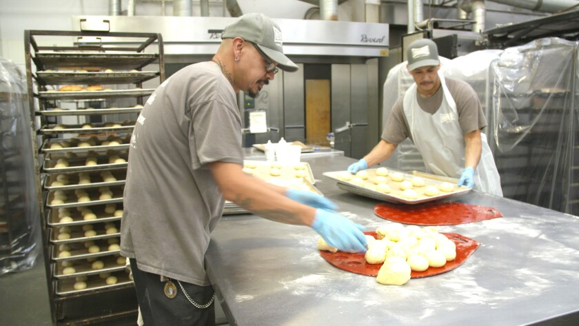 Luis Bahena, left, and Ernie Jimenez make baked goods for sale in the bakery at Homeboy Industries in downtown Los Angeles.